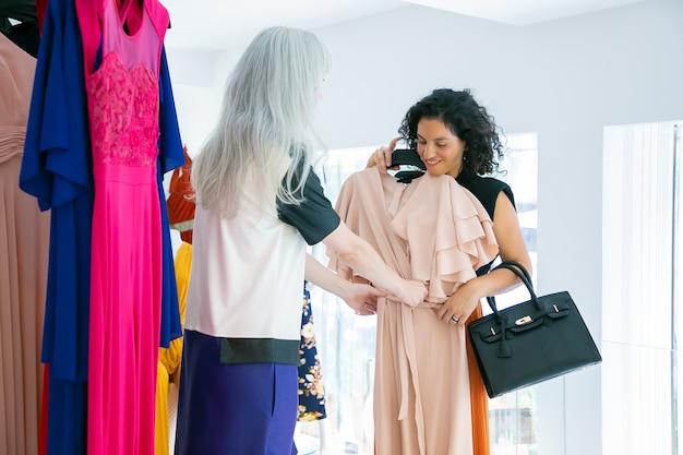 Mode winkel verkoper helpen klant om doek te kiezen en jurk met hanger toe te passen op vrouw. openhartig schot. modewinkel of winkelconcept