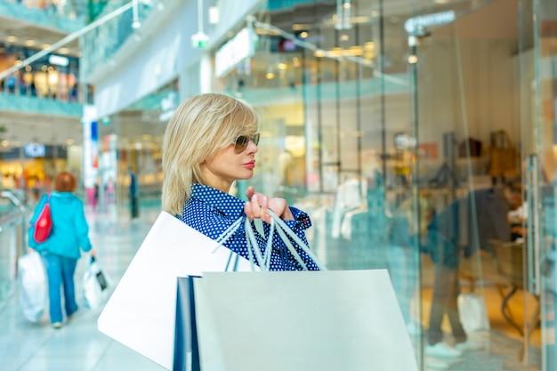 Mode winkelen meisje portret. schoonheid vrouw met boodschappentassen in winkelcentrum. shopper.