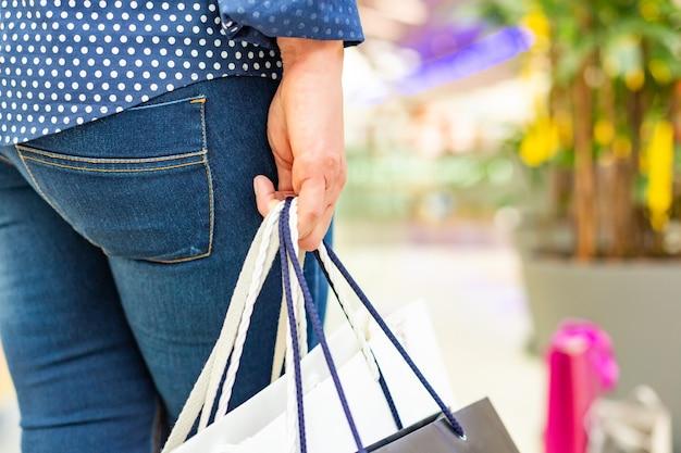 Mode winkelen meisje portret. schoonheid vrouw met boodschappentassen in winkelcentrum