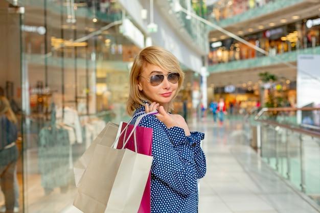 Mode winkelen meisje portret. schoonheidsvrouw met het winkelen zakken in winkelcomplex. shopper. verkoop.