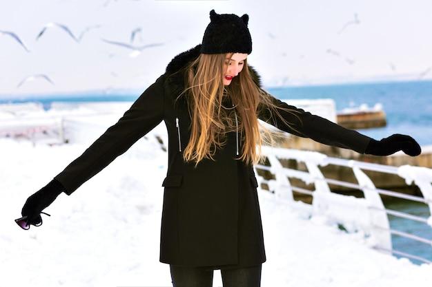Mode winter portret van elegante blonde dame vrouw, geniet van koude sneeuwtijd aan zee, ijs en winderig, zwarte jas, grappige hoed, lange haren, sensuele stemming, alleen reizen, wintermode.