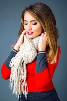 Mode winter portret van mooie blonde vrouw met sexy rokerige make-up, heldere trendy smart casual trui, zwarte leren broek en grote gezellige warme beige sjaal dragen.