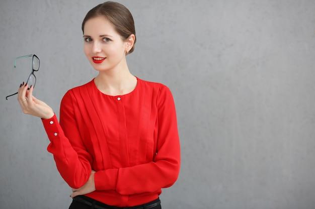 Mode zakelijke vrouw met een rood shirt en bril portret, zonnebril in zijn hand houden