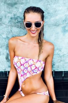 Mode zomerbeeld van sexy jonge vrouw, gekleed in heldere gedrukte bikini en vintage zonnebril, nat lichaam en haren, stedelijke muur, vakantiestijl.