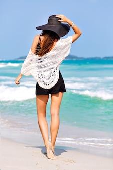 Mode zomerbeeld van vrouw poseren terug, in de buurt van blauwe zeewater, mooie zonnige zomerdag, ontspannen einde genieten van vrijheid, vreugde, geluk, heldere kleuren