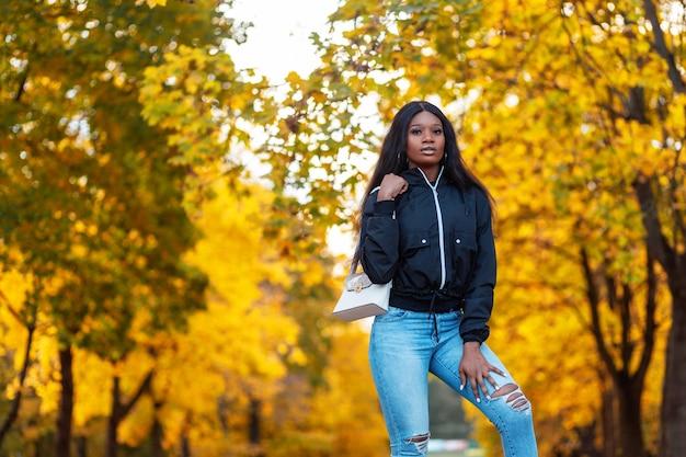 Mode zwart amerikaans vrouwenmodel in stijlvol casual jasje met spijkerbroek en tas loopt in geweldig herfstpark met gele herfstbladeren