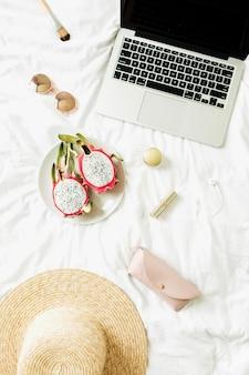 Modeaccessoires voor dames, bril, lippenstift, strohoed, koptelefoon met laptop en exotisch drakenfruit op bed met wit linnengoed