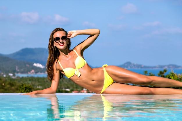 Modebeeld van prachtige sexy vrouw met slank fit lichaam ontspannen in de buurt van het overloopzwembad, op een exotisch tropisch eiland, warme dagen, bikini, luxe leven, vakantiestemming.