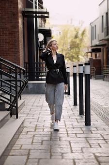 Modeblogger die op straat loopt met een oversized zwarte jas, grijze spijkerbroek en trendy witte sneakers