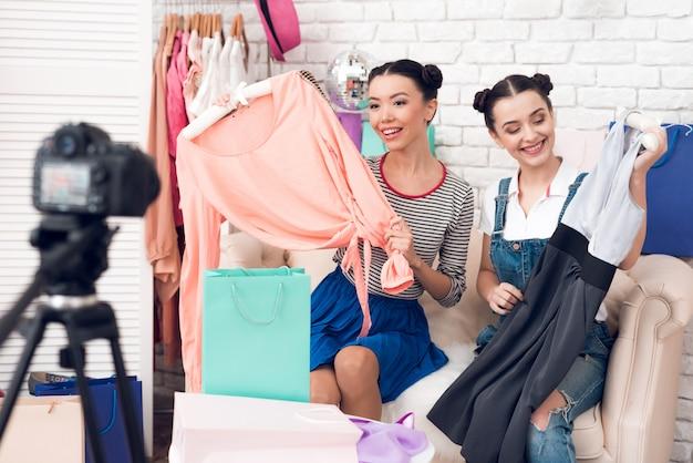 Modebloggermeisjes trekken kleurrijke jurkjes uit kleurrijke tassen