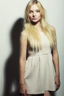 Modefoto van jonge prachtige vrouw in witte jurk