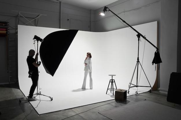 Modefotografie in een fotostudio. professionele mannelijke fotograaf die foto's maakt van een mooi vrouwenmodel op camera, backstage