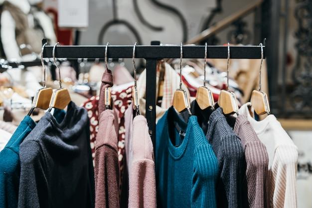 Modekleding op hangers op de show