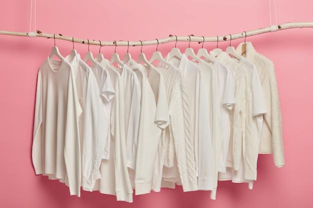 Modekleding van witte kleur, gebreide patronen, hangend aan rekken voor weergave. rij stevige outfits in kleerkast.