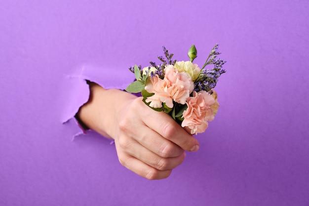 Modekunst hand met bloemen wordt door een gat in de papieren achtergrond gestoken