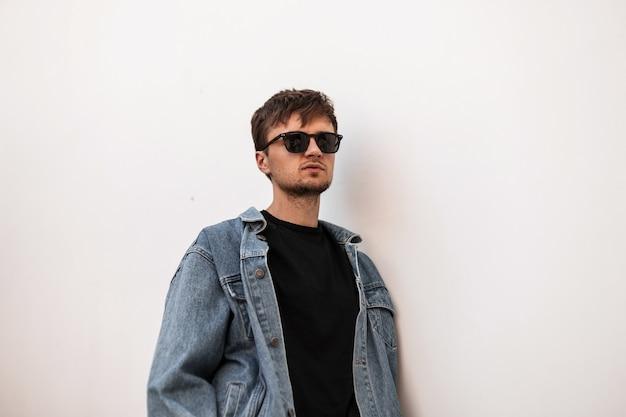 Model amerikaanse jongeman hipster in een modieuze blauwe denim jasje in een zwart t-shirt in vintage zonnebril buiten in de buurt van een witte muur. aantrekkelijke stedelijke kerel rust in de stad. stijlvolle herenkleding.