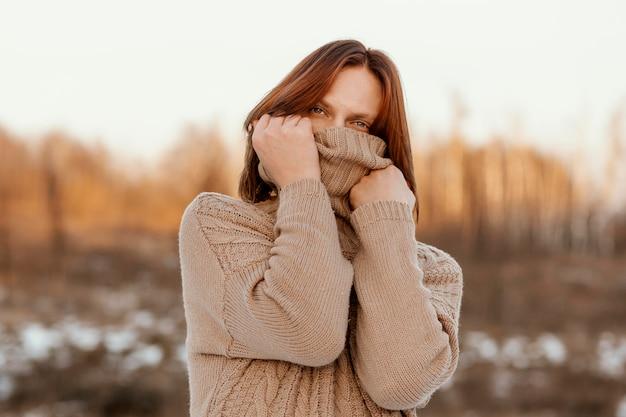 Model bedekkend gezicht met een beige trui