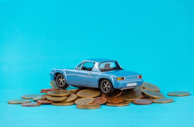 Model blauw parkeerterrein op stapel gouden muntstukken