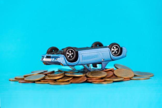 Model blauwe auto ten val gebrachte samenstelling op stapel gouden muntstukken