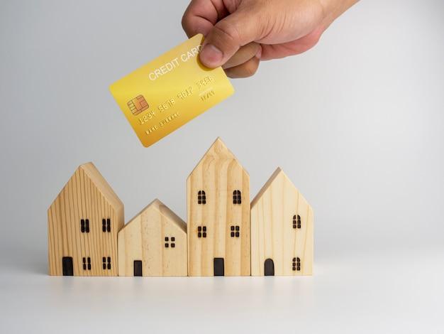 Model blokhuis en hand van de creditcard van de houder van de persoon. huisvesting bedrijfsconcept.