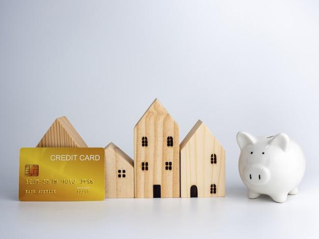 Model blokhuis en spaarvarken en creditcard. huisvesting bedrijfsconcept.