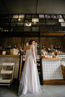 Model brunette in kort haar poseren in een witte trouwjurk