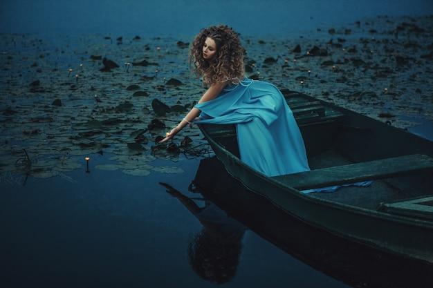 Model draagt blauwe jurk is poseren in een boot op het water