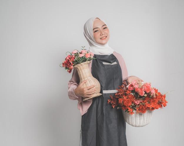 Model draagt hijab, met een bloem op een beige geïsoleerde achtergrond. stijlvolle moslimvrouw met een emmer met bloem