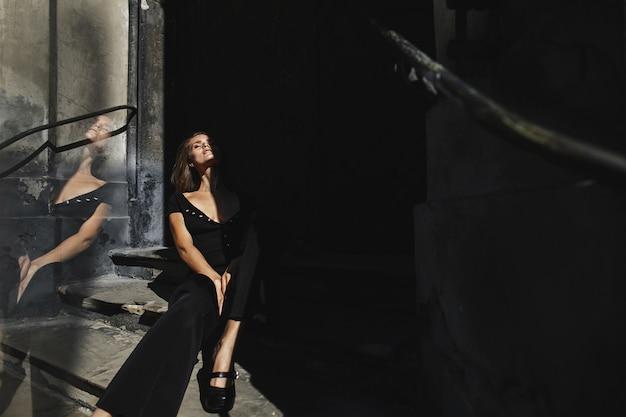 Model gekleed in het zwart outfit zit op de oude trap van het gebouw