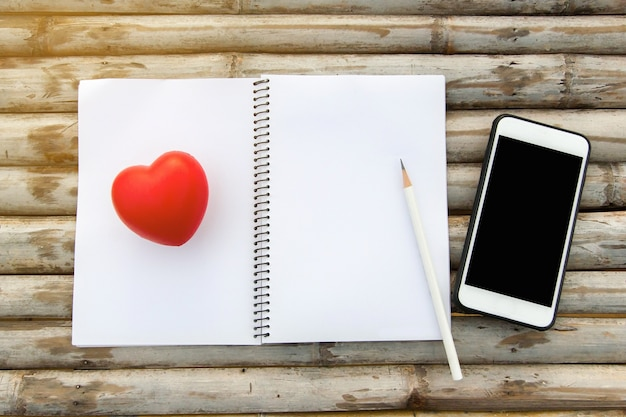 Model hoogste mening van notitieboekje met potloodglas en hart rubbermodel op bamboe houten lijst