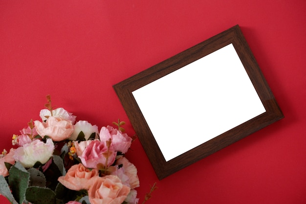 Model houten fotokader met ruimte voor tekst of beeld op rode achtergrond en bloem.