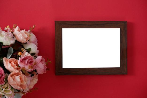 Model houten fotolijst met ruimte voor tekst of afbeelding op rode achtergrond en bloem.