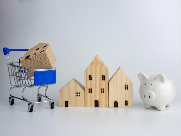 Model houten huis en spaarvarken en winkelwagentje. huisvesting bedrijfsconcept.