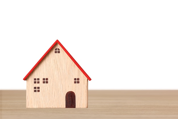 Model houten huizen op houten bureau op witte achtergrond