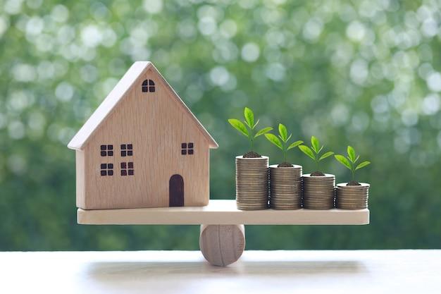 Model huis met bomen groeien op stapel munten geld op houten schaal wip met natuurlijke groene achtergrond