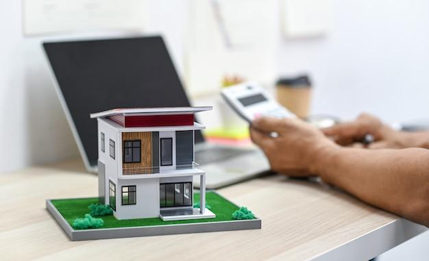 Model huis op een tafel met een onscherpe achtergrond van een persoon met behulp van rekenmachine en een laptop op tafel, onroerende goederenuitgaven.