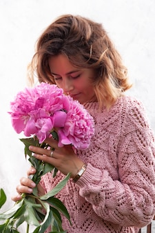 Model in bruine gebreide trui met natuurlijke make-up en roze pioenrozen