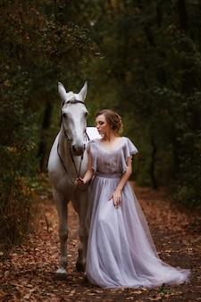 Model in een delicate jurk met een wit paard in de buurt in een prachtig groen bos.