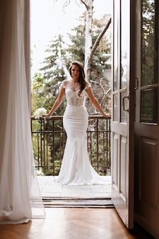 Model in een elegante trouwjurk op het balkon