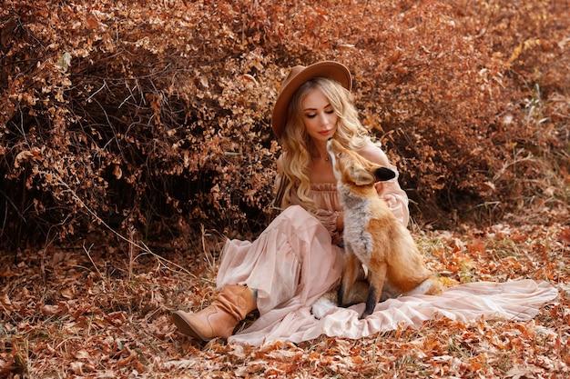 Model in een jurk met een vos in de herfst