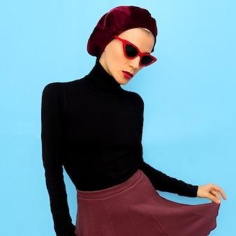 Model in een modeaccessoire baret en zonnebril. vintage-stijl