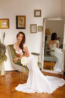 Model in een trouwjurk op een fauteuil