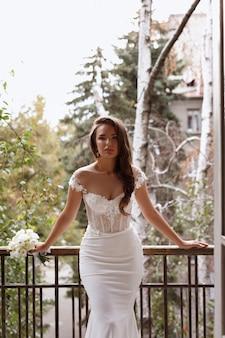 Model in een trouwjurk op het balkon
