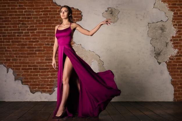 Model in elegante jurk, vrouw poseren in vliegende zijden doek zwaaien op wind