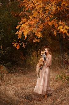 Model in het herfstbos met een vos