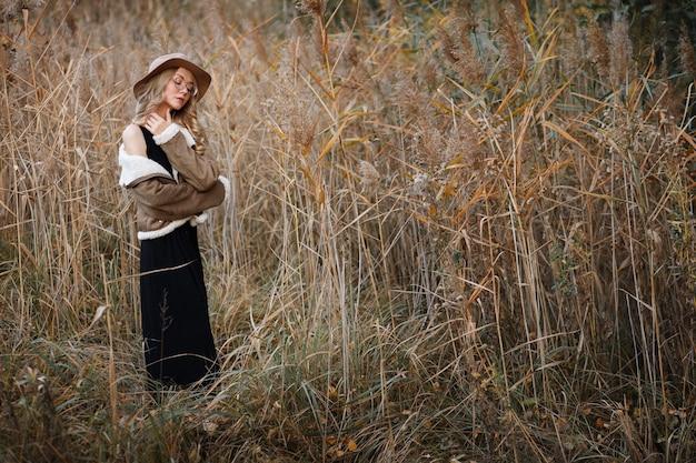 Model in hoed en jas vallen poseren in de natuur