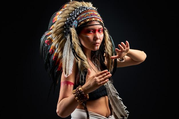 Model in indiase outfit en kleurrijke make-up poseren vooraan, met veren op het hoofd