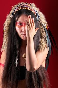 Model in indisch dragen en kleurrijke make-up poseren, met veren op het hoofd. outfit van inheemse volkeren van amerika, etnische vrouw die de helft van het gezicht sluit
