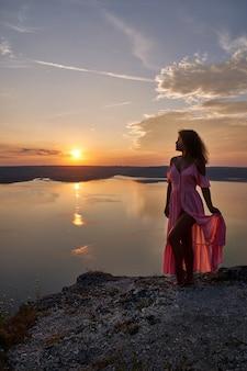 Model in lange jurk poseren op de achtergrond van de zonsondergang.