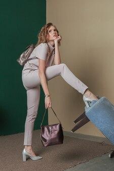 Model in lichtroze staande op de rand van een omgekeerde stoel met paarse tas.